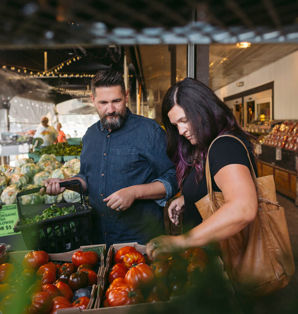 a man and a woman shop for vegetables at a store