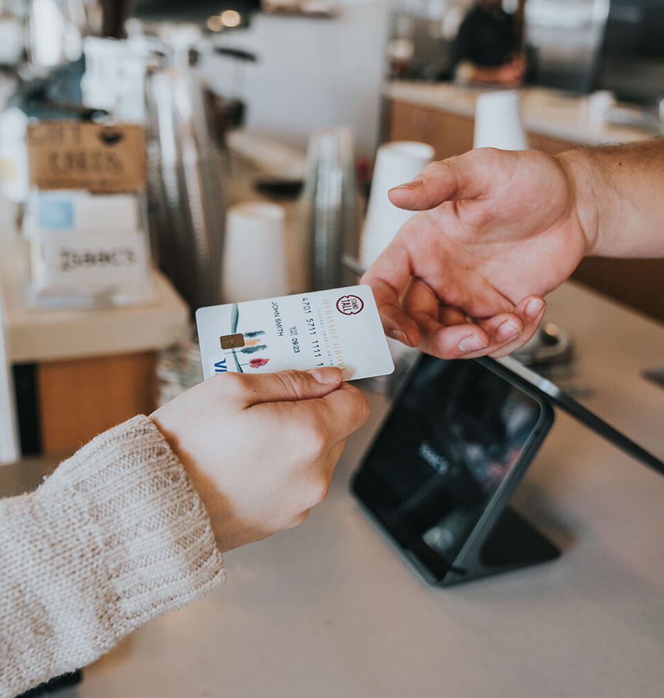 a hand gives another hand a Heritage Grove VISA credit card