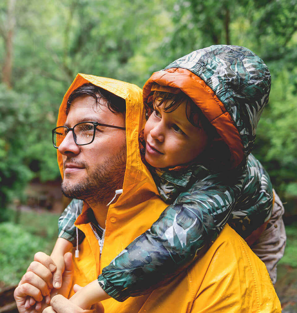 a man in a raincoat holds his kid on his shoulders