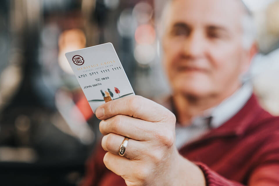 man holds out a Heritage Grove VISA credit card