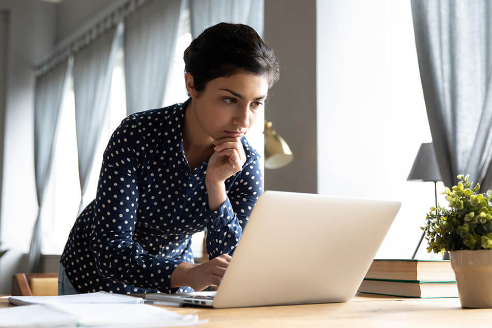 a woman in a blue polka dot blouse hunches over a laptop
