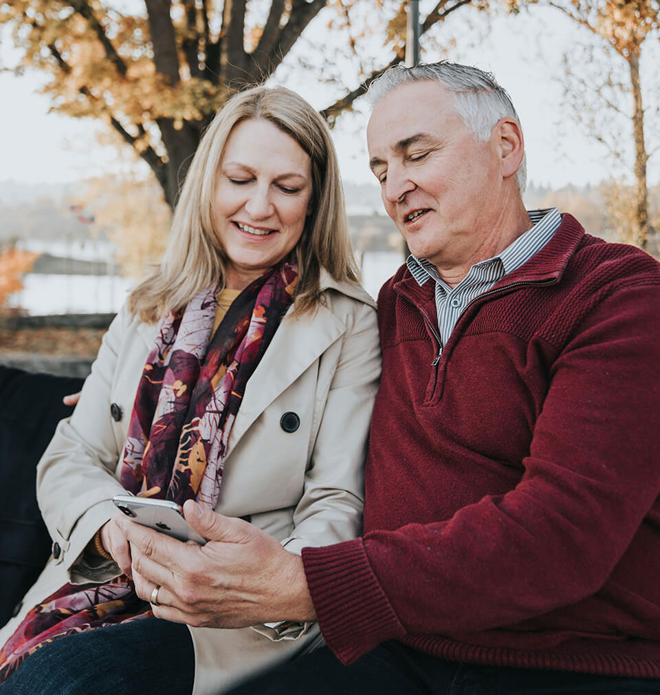 an older couple stare at their phone in bemusement