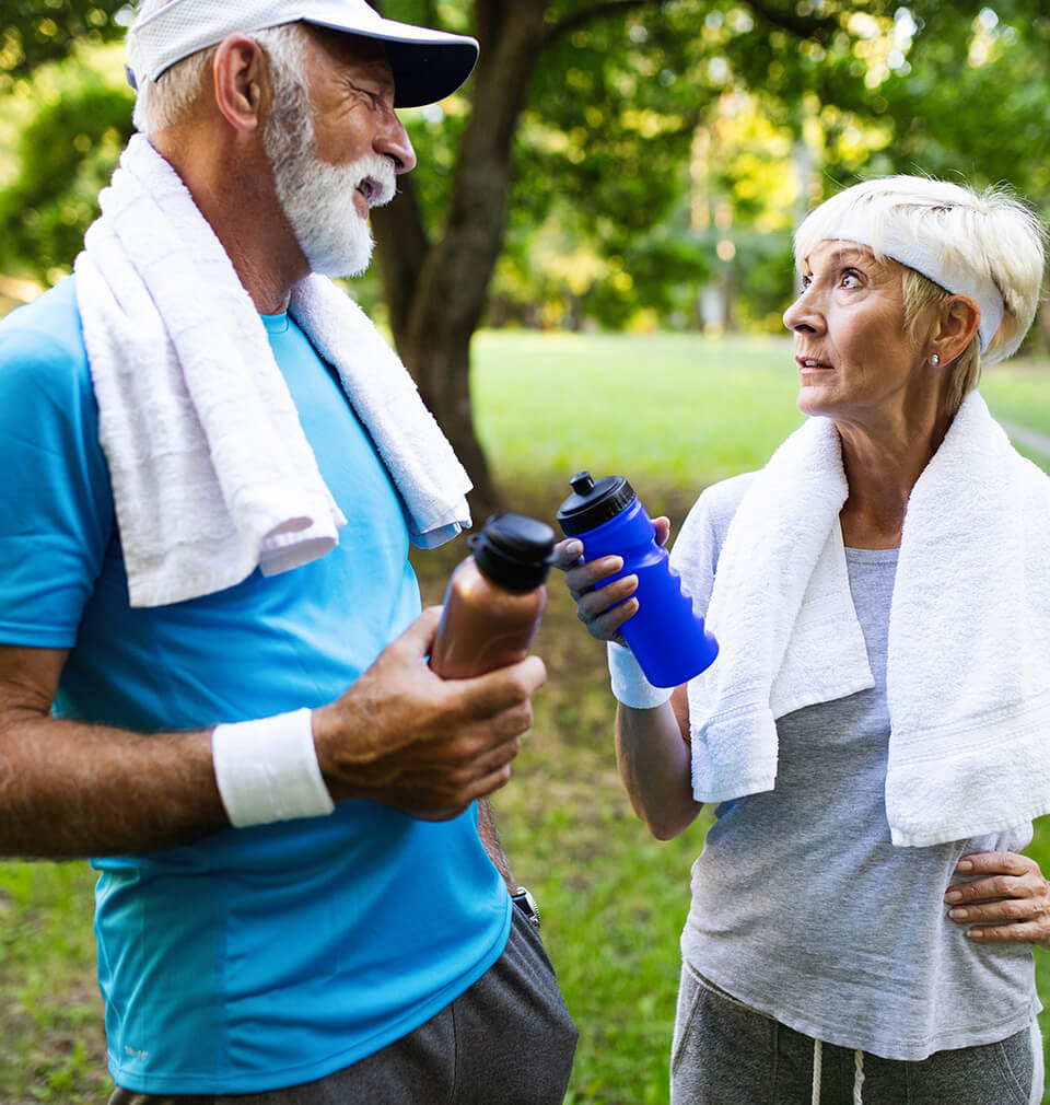 older couple in running outfits talk while holding water bottles
