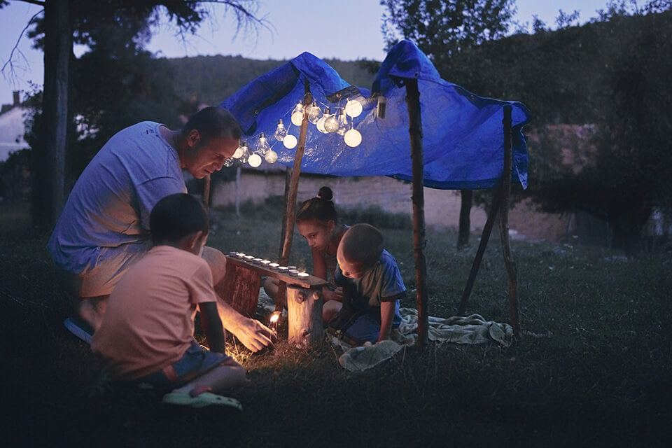 a father lights a candle with his kids under a blue tarp