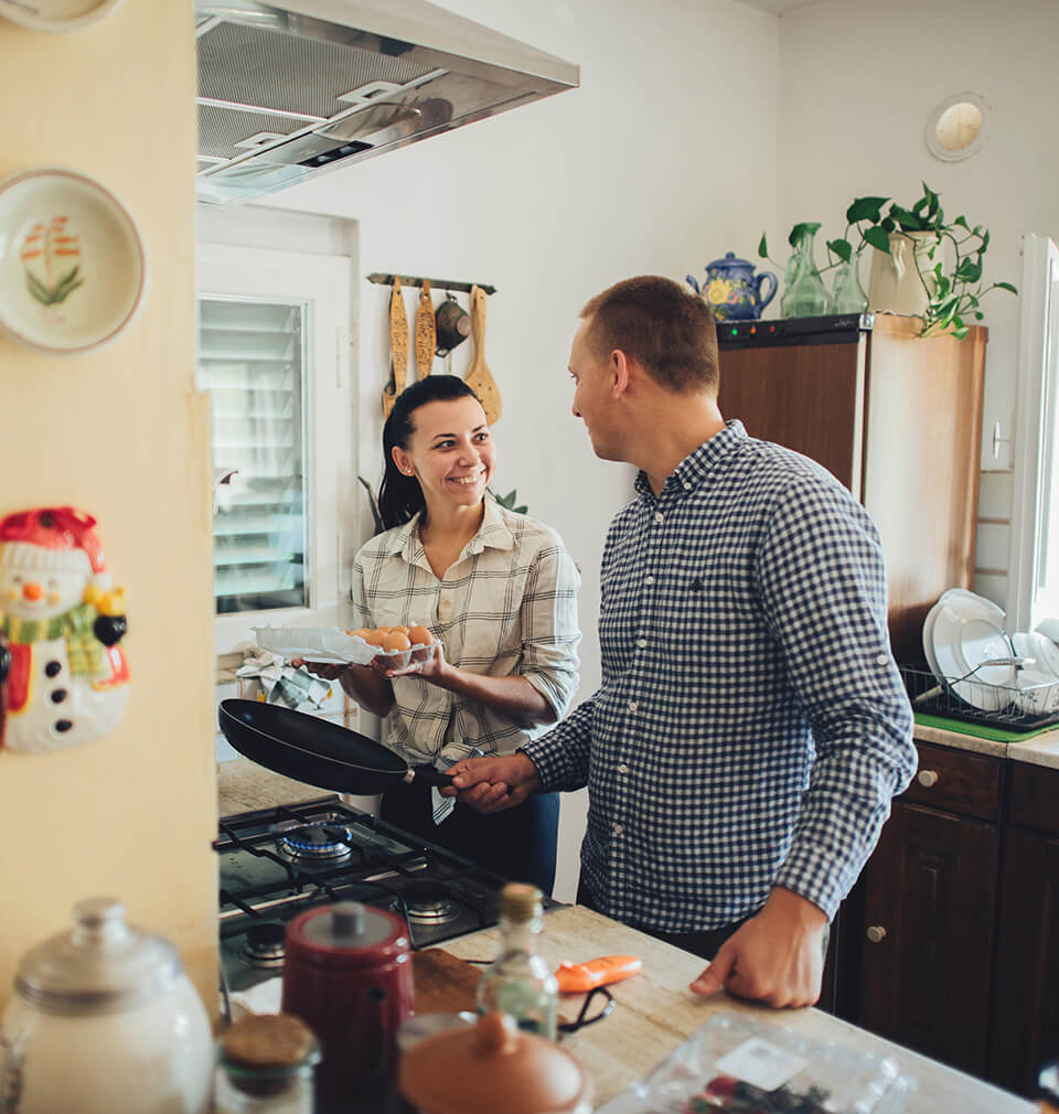 a woman smiles at a man who is cooking eggs