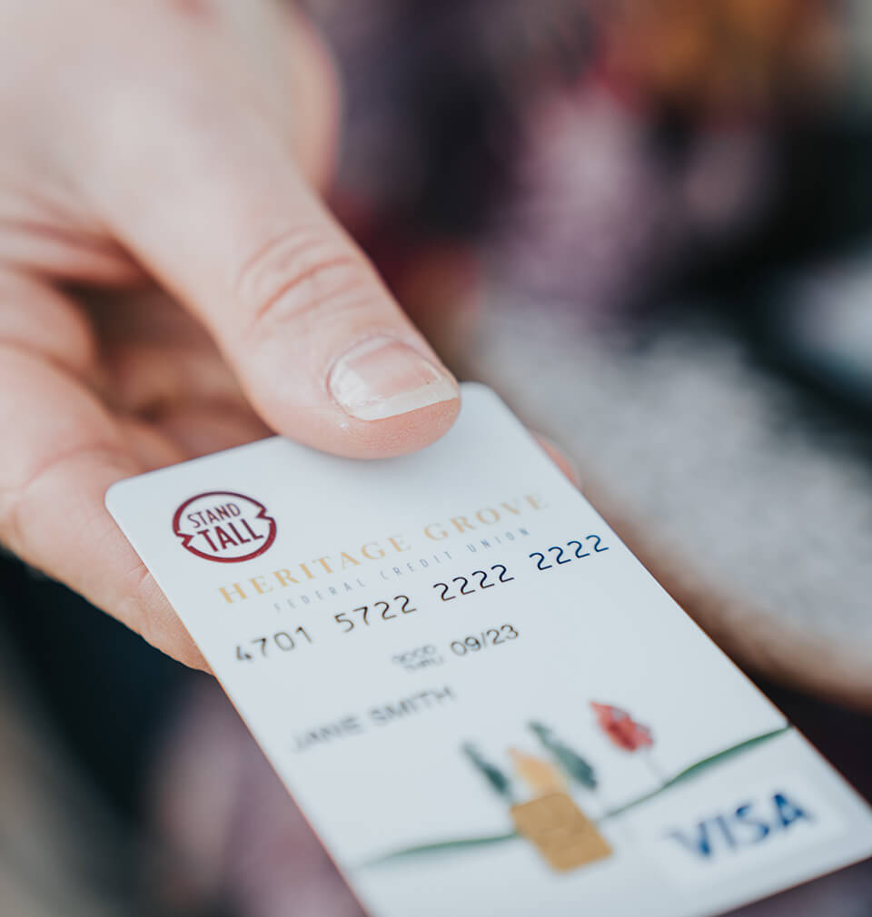 hand holding out a VISA debit card