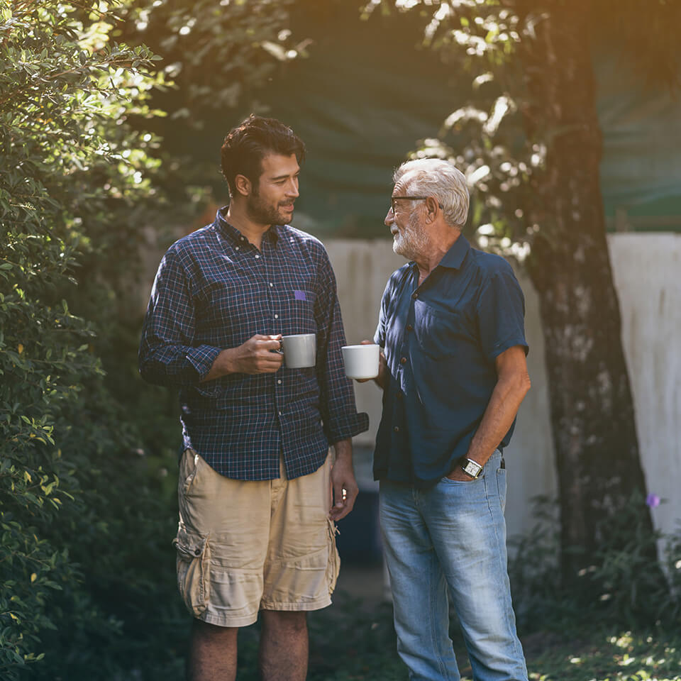 A father and son talking holding coffee