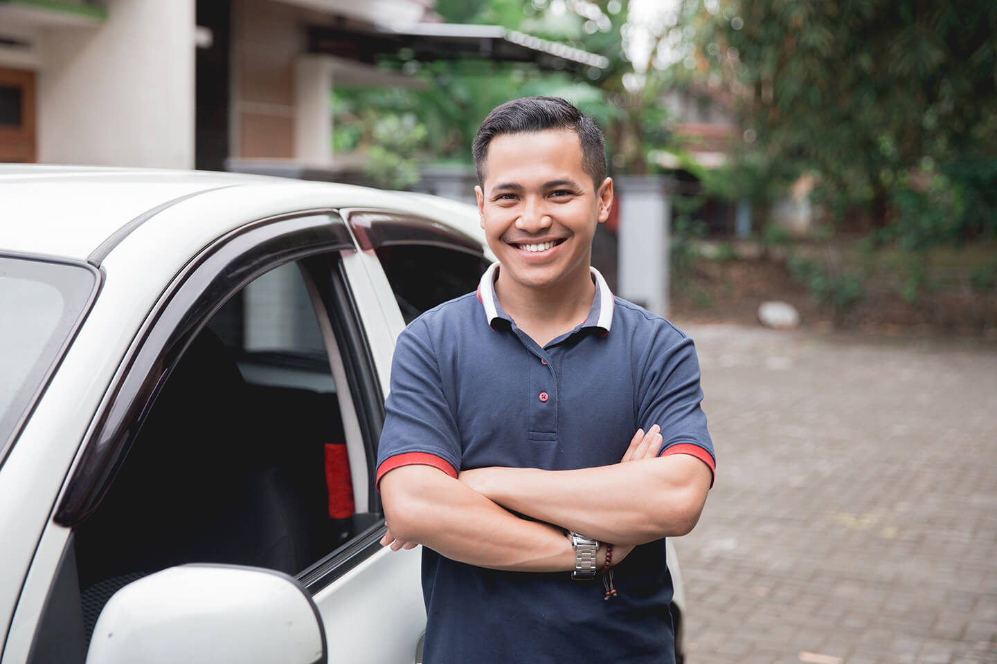 man in front of white car
