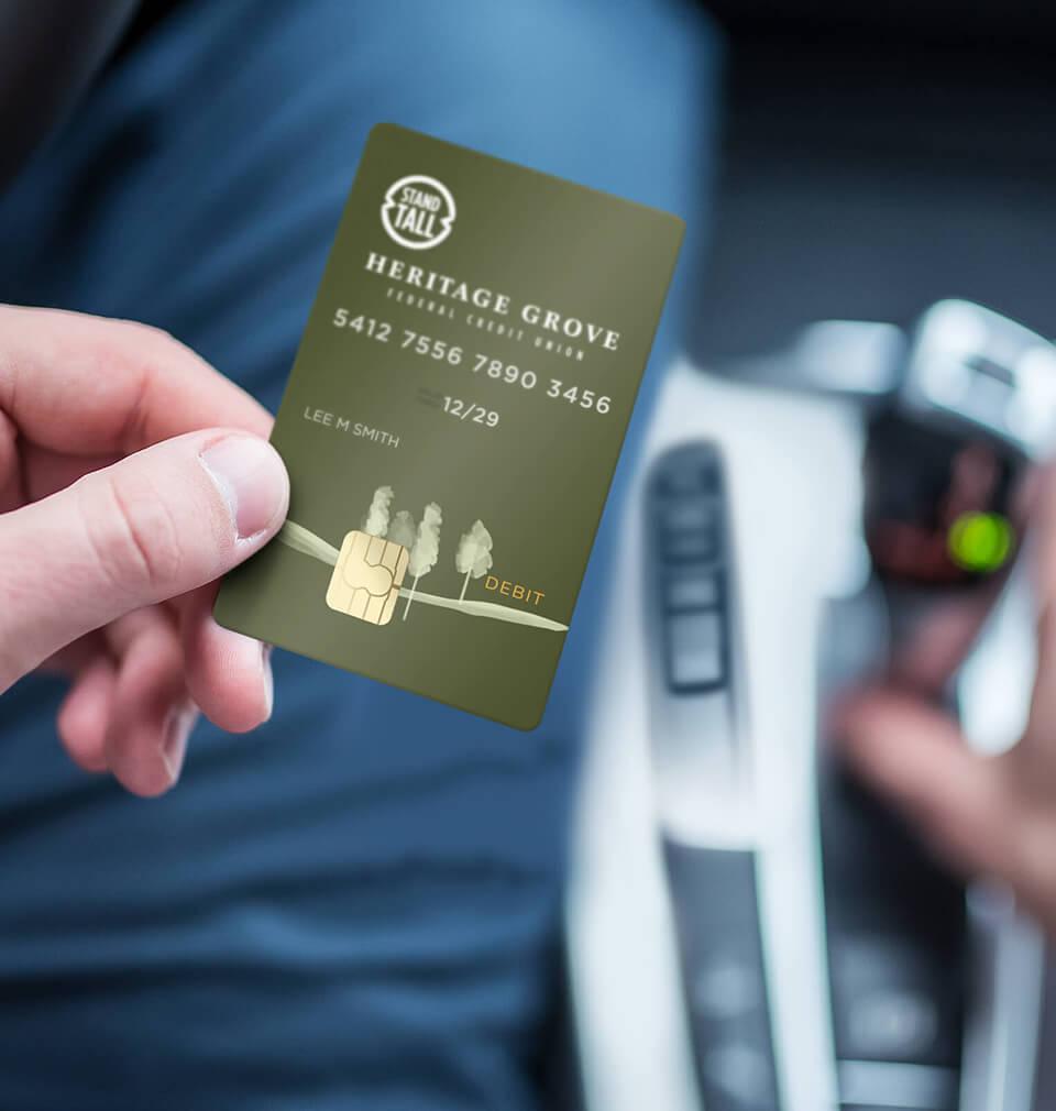 finger holding Heritage Grove VISA Debit Card